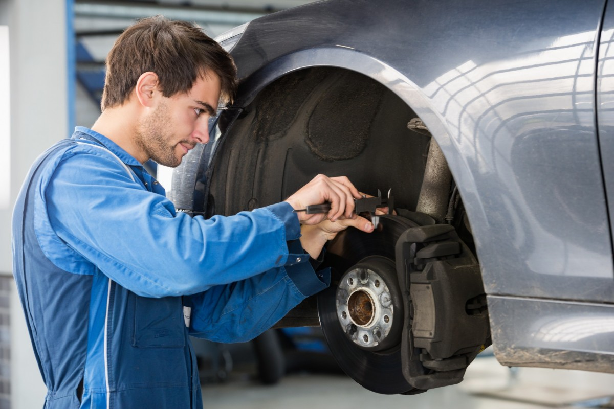 mechanic working on the brakes of a car